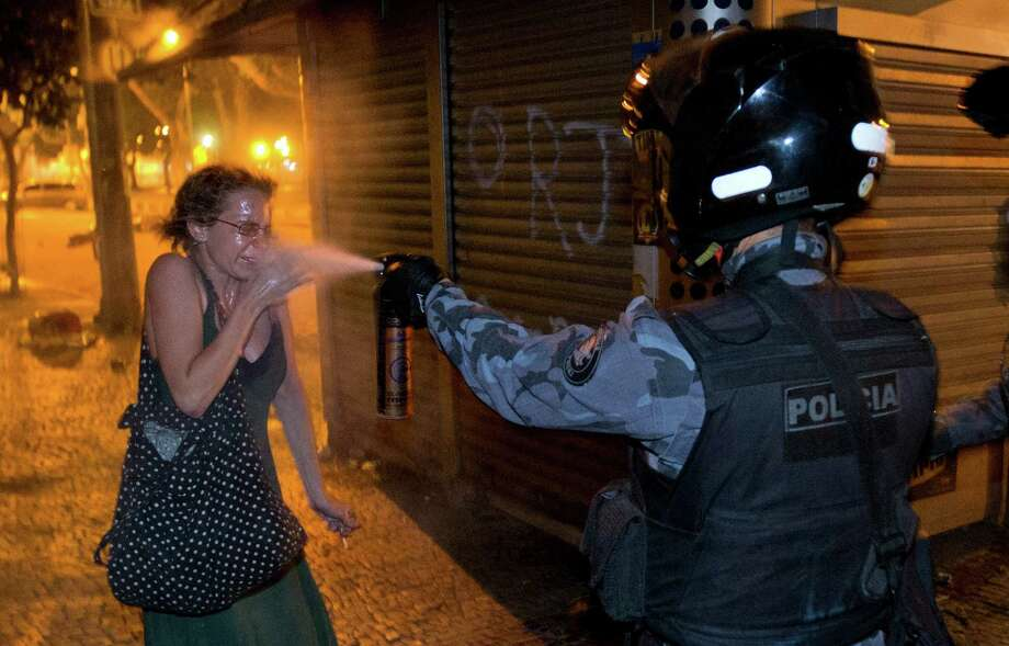 This June 17, 2013 photo, a military policeman pepper sprays a protester during a demonstration in Rio de Janeiro.  Protesters amassed in at least seven Brazilian cities Monday for another round of demonstrations voicing disgruntlement about life in the country, raising questions about security during big events like the current Confederations Cup and a papal visit next month. Photo: AP