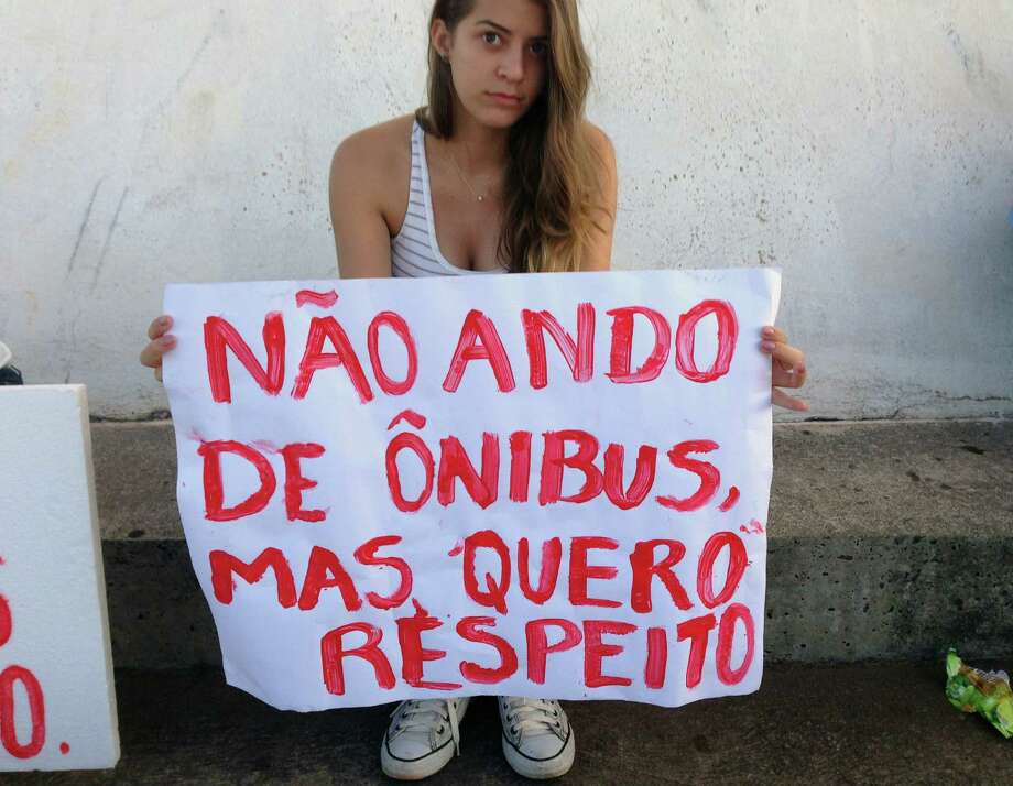"Lorena Dias poses for a photo holding a sign that reads in Portuguese; ""I don't ride the bus, but I want respect,"" at an anti-government protest, in Brasilia, Brazil, Thursday, June 20, 2013.  The 15-year-old student says, ""This is the time to change so much that is wrong in Brazil and it's young people who are leading the way. I see a sign of hope in this movement."" Photo: AP"