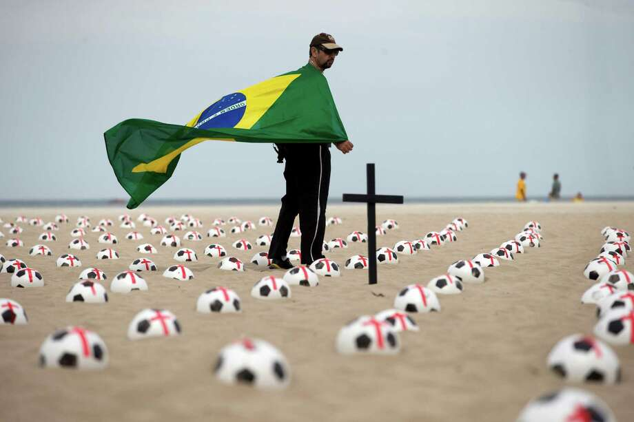 A man holds a Brazilian flag while he walks amid soccer balls painted with a red cross during a protest against spending on stadiums for the Confederation Cup and the 2014 World Cup at the Copacabana beach, in Rio de Janeiro, Brazil, Saturday, June 22, 2013. Demonstrators once again took to the streets in Brazil on Saturday, continuing a wave of protests that have shaken the nation and pushed the government to promise a crackdown on corruption and greater spending on social services. Photo: AP