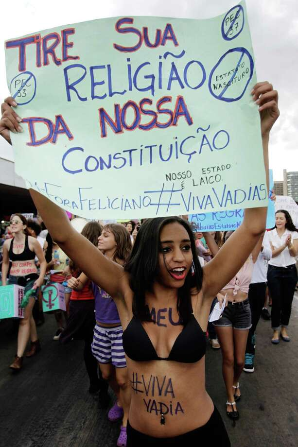 "A demonstrator holds up a sign that reads in Portuguese ""Get your religion out of our constitution"" during a protest against sexism and in defense of women's rights in Brasilia, Brazil, Saturday, June 22, 2013. Demonstrators once again took to the streets of Brazil on Saturday, continuing a wave of protests that have shaken the nation and pushed the government to promise a crackdown on corruption and greater spending on social services. Photo: AP"