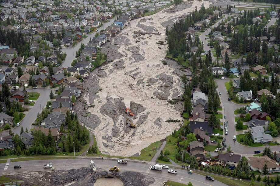In this aerial photo, the flooded Cougar Creek runs through Canmore, Alberta, on Friday June 21, 2013. Communities throughout southern Alberta are dealing with overflowing rivers that have washed out roads and bridges, inundated homes and turned streets into dirt-brown tributaries. Photo: AP