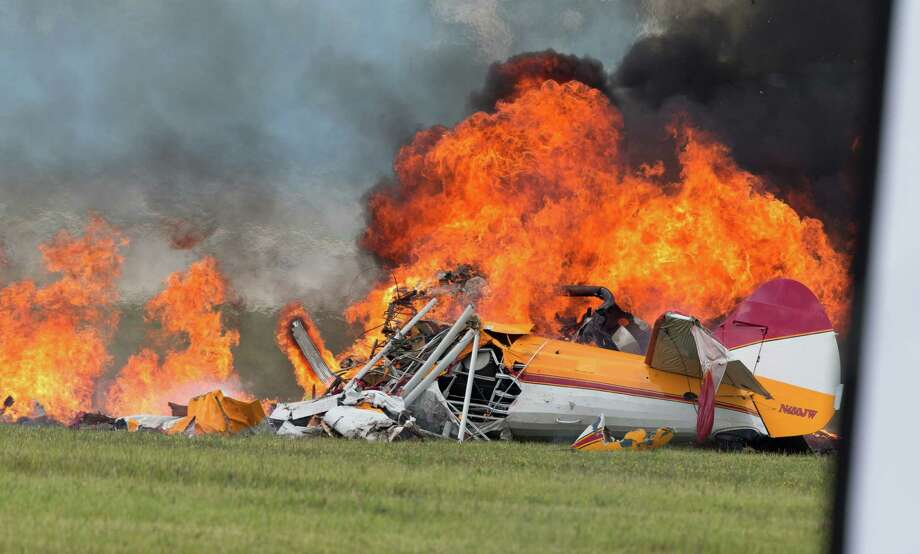 Smoke rises from a stunt plane after it crashed during a wing walker's performance at the Vectren Air Show, Saturday, June 22, 2013, in Dayton, Ohio. The crash killed the pilot and the wing walker instantly, authorities said. (AP Photo/Thanh V Tran)  Photo: AP