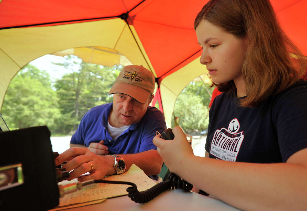 Tony O'Connor helps Hayley Siegel, 17, reach a ham radio station in San Diego at the Get on the Air station during the Stamford Amateur Radio Association's field day at the Stamford Museum & Nature Center on Sunday, June 23, 2013. Siegel recently passed the Amateur Radio Technician License Exam and communication with the San Diego station was her first time making contact over the radio.