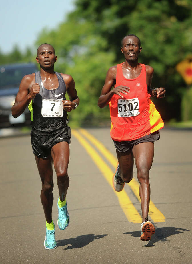 Race leaders Shadrack Kipkorir Kiy, left, and Eric Chirchir, both from Kenya, run stride for stride down Old Field Road in the Fairfield Half Marathon in Fairfield, Conn. on Sunday, June 23, 2013. Chirchir won the race in 1:05:58 with Kiy placing second in 1:06:15. Photo: Brian A. Pounds / Connecticut Post