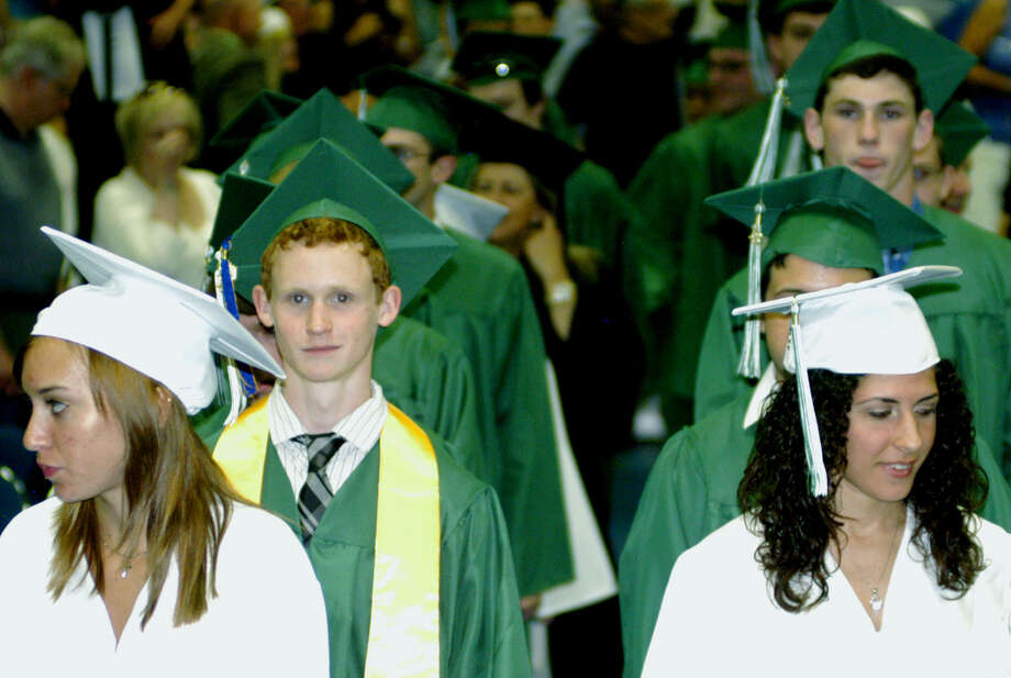 Nicole DeStefano, left, Spencer Devlin, Taylor Daniels, right, and fellow members of the Class of 2013 experiences the processional during New Milford High School's commencement exercises at the O'Neill Center on the campus of Western Connecticut State University in Danbury. June 22, 2013 Photo: Norm Cummings