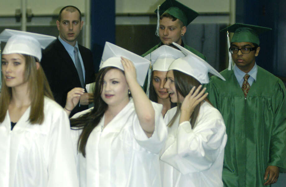 Savannah Woods, left, Haley Wright and fellow members of the Class of 2013 experience the processional during New Milford High School's commencement exercises at the O'Neill Center on the campus of Western Connecticut State University in Danbury. June 22, 2013 Photo: Norm Cummings