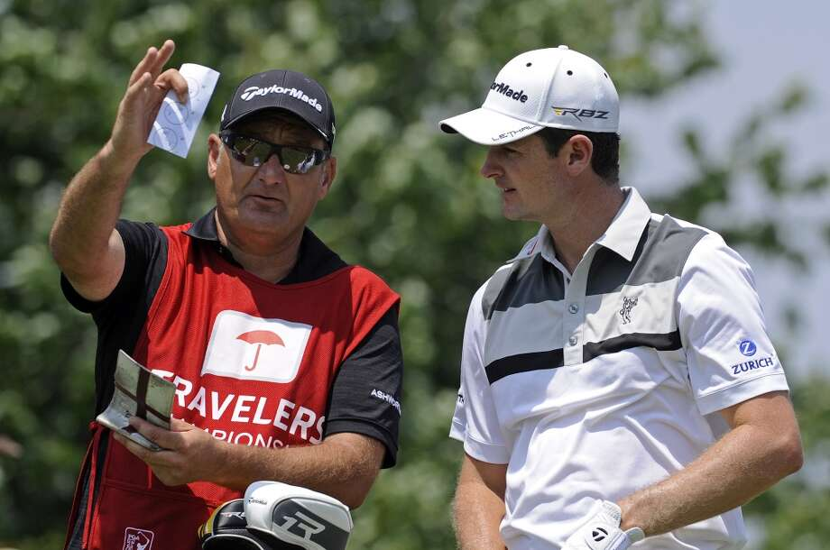Justin Rose, right, of England, speaks with his caddie on the second hole during the final round of the Travelers Championship golf tournament in Cromwell, Conn., Sunday, June 23, 2013. (AP Photo/Fred Beckham)