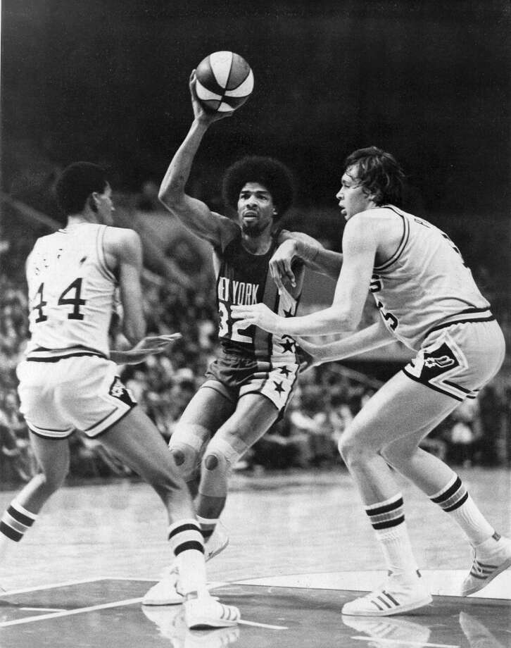 The Spurs' George Gervin (left) and Billy Paultz play defense on the Nets' Julius Erving during a 1975-76 ABA game.
