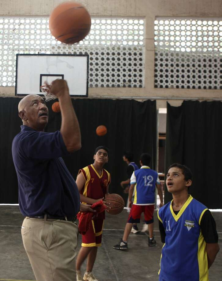 U.S. basketball Hall of Famer George Gervin spins the ball as Indian students watch at a coaching clinic in Mumbai, India on Feb. 24, 2011. Gervin visited Mumbai and New Delhi as part of a sports envoy program of the U.S. Department of State and the NBA.