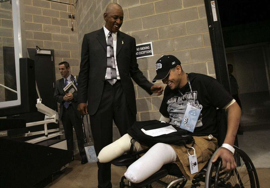 Former Spur George Gervin greets his guest, Alex Del Rio, a San Antonian who was injured while serving in Iraq, before Game 6 of the NBA Finals at the SBC Center on June 21, 2005.
