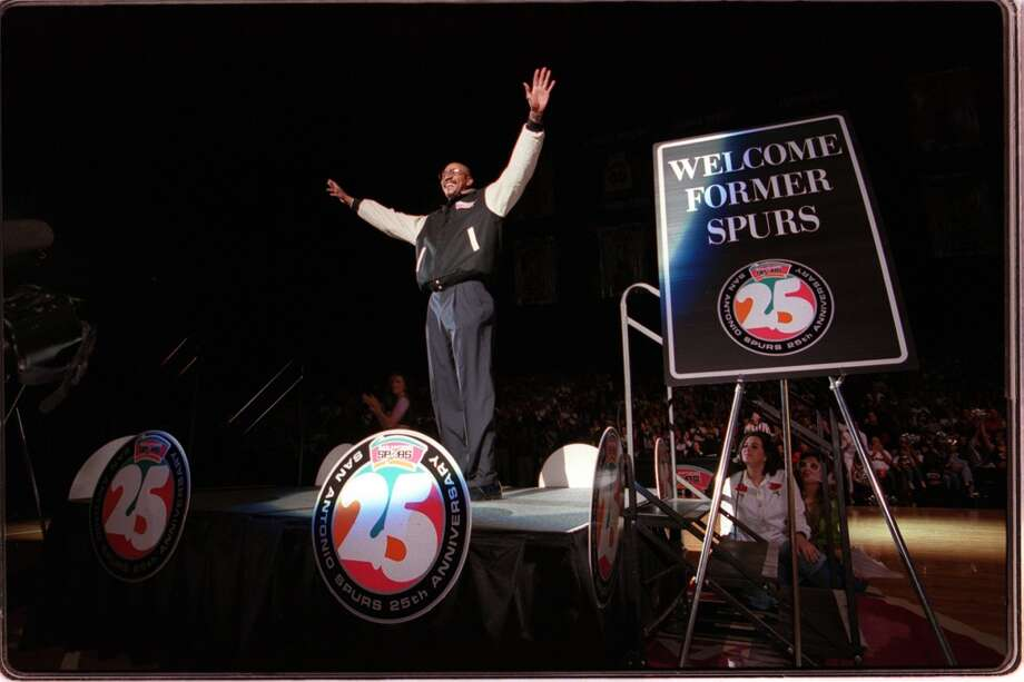 With the roar of the crowd, Spurs' legend George Gervin raises his arms to receive the applause as former players were honored at half-time of the Spurs-SuperSonics game on Apri 10, 1998.