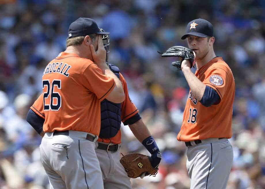 Astros pitching coach Doug Brocail speaks with pitcher Jordan Lyles and catcher Jason Castro.