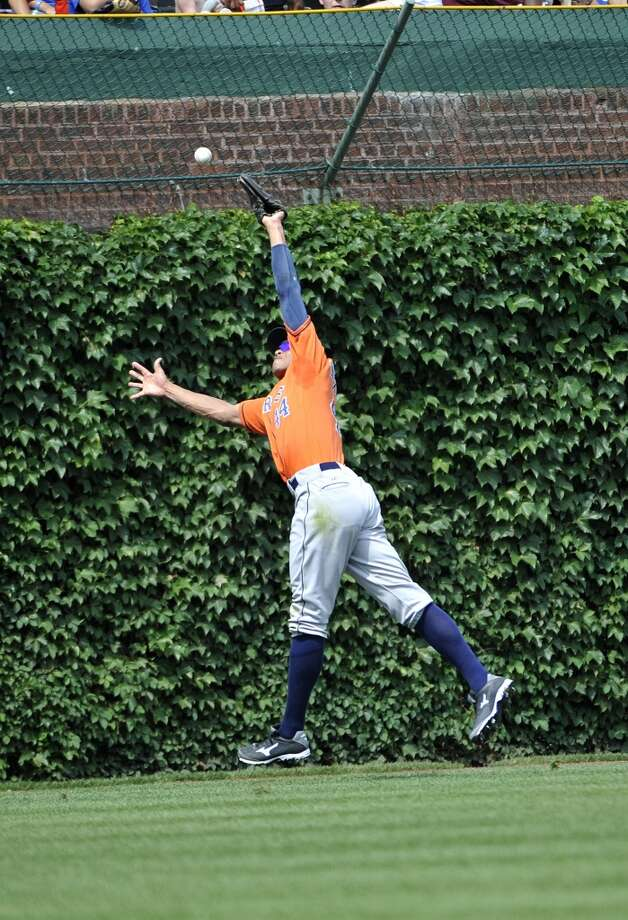 J.D. Martinez of the Astros can't catch a ball for an out against the Cubs at Wrigley Field.