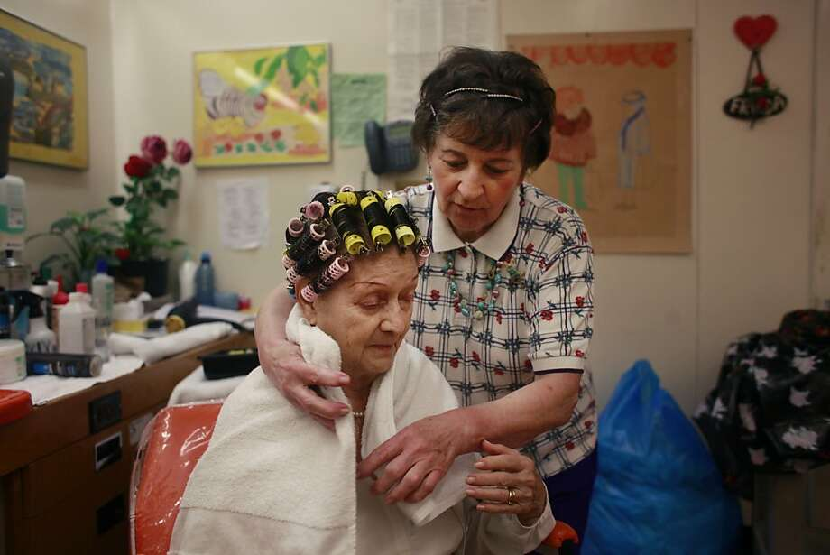 Frieda Saenz (right) wraps a towel around Dulce Martinez in the beauty salon at the Jewish Home of San Francisco. The facility is trimming services amid Medi-Cal cuts and requests for retroactive payments. Photo: Lea Suzuki, The Chronicle