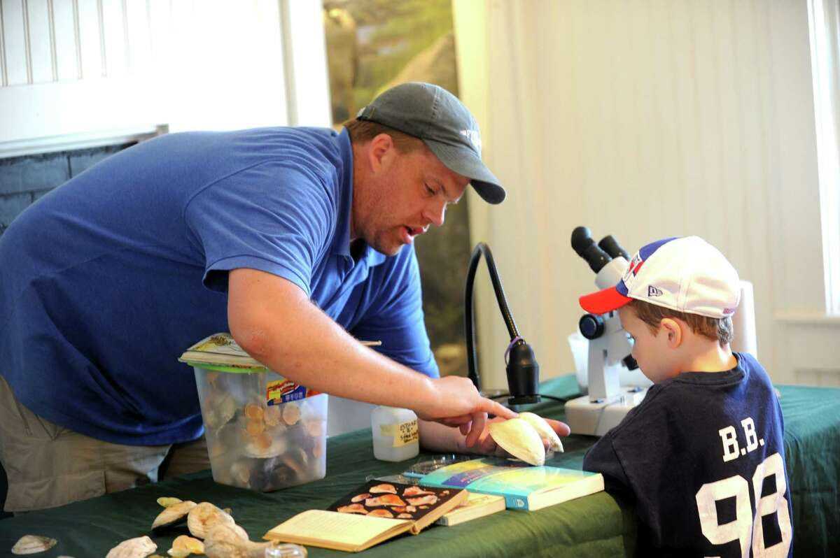 Teacher Robert Otto, shows Brett Sylvester, 5, different shells at the Floren Family Environmental Center during the Greenwich Shellfish Commission's Experience the Sound event, at Greenwich Point, in Greenwich, Conn., Sunday, June 23, 2013.