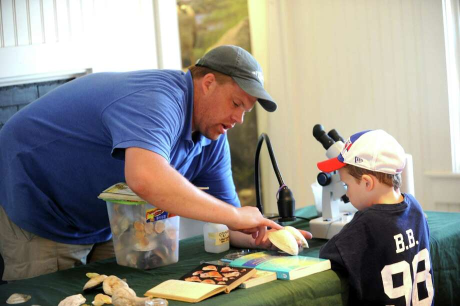 Teacher Robert Otto, shows Brett Sylvester, 5, different shells at the Floren Family Environmental Center during the Greenwich Shellfish Commission's Experience the Sound event, at Greenwich Point, in Greenwich, Conn., Sunday, June 23, 2013. Photo: Helen Neafsey / Greenwich Time