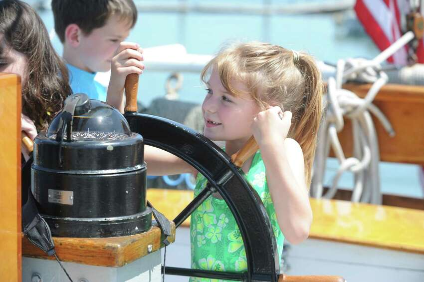 Isabella Wilson, 6, of Greenwich, plays with the wheel of the Soundwaters schooner from the Greenwich Shellfish Commission's Experience the Sound event, at Greenwich Point, in Greenwich, Conn., Sunday, June 23, 2013.