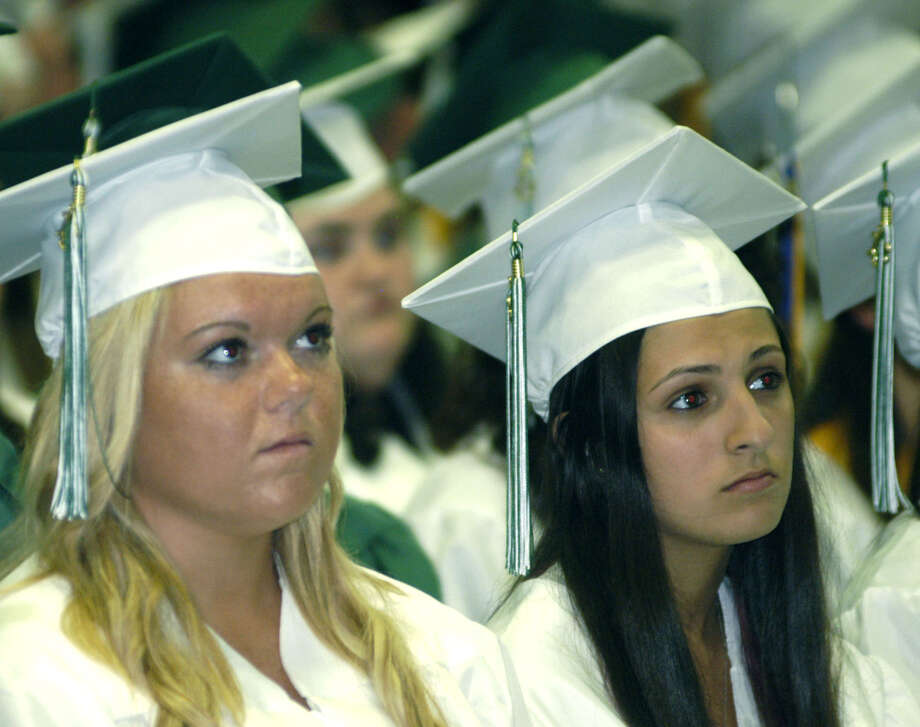 Briana Celio, left, and Arianna Cecchini listen to a classmate's speech during New Milford High School's commencement exercises at the O'Neill Center on the campus of Western Connecticut State University in Danbury. June 22, 2013 Photo: Norm Cummings