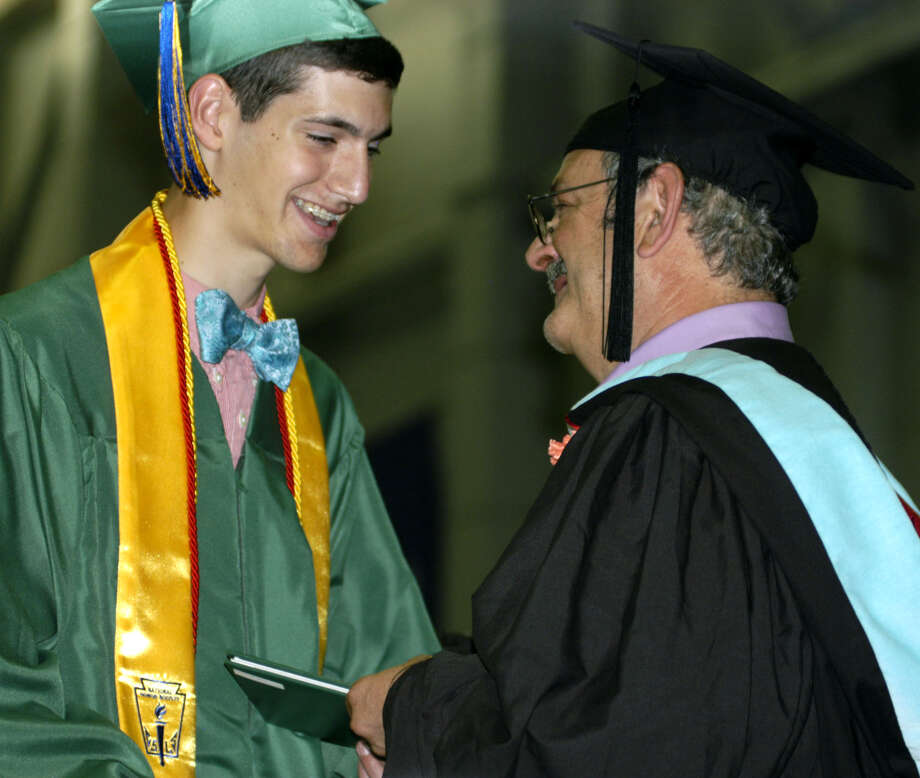 Class of 2013 president Ben Lawson happily accepts his diploma from his proud father, Board of Education member David Lawson, during New Milford High School's commencement exercises at the O'Neill Center on the campus of Western Connecticut State University in Danbury. June 22, 2013 Photo: Norm Cummings