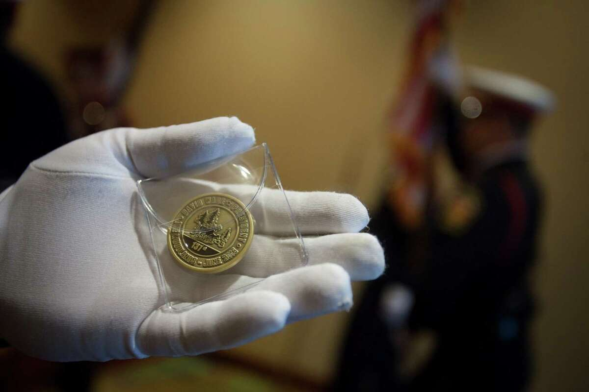 Stuart Norman, of the Montgomery County Fire Chiefs Association Honor Guard, shows off a challenge coin commemorating the event as the State Firemen's and Fire Marshals' Association honored 22 Texas Firefighters who died in the line of duty.