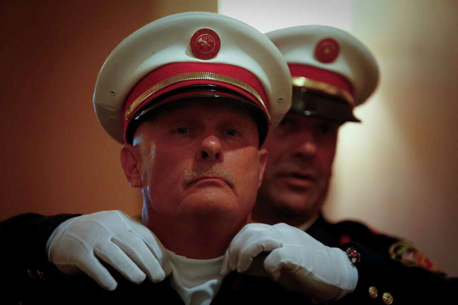 Stuart Norman, of the Montgomery County Fire Chiefs Association Honor Guard, adjusts the collar of James R. Wathen as he and others prepare to present as the State Firemen's and Fire Marshals' Association honored 22 Texas Firefighters who died in the line of duty, including recent Houston firefighters and the volunteer firefighters in West, TX.  Photo: Eric Kayne, For The Chronicle / ©Eric Kayne 2013
