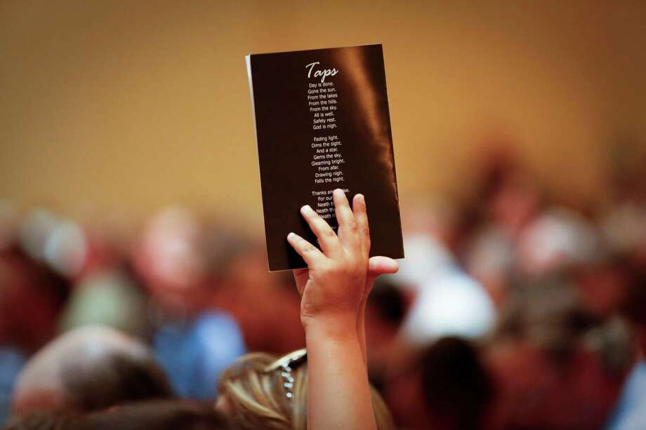 A child holds up a program with the lyrics to Taps printed on it as the State Firemen's and Fire Marshals' Association honored 22 Texas Firefighters who died in the line of duty, including recent Houston firefighters and the volunteer firefighters in West, TX. Photo: Eric Kayne, For The Chronicle / ©Eric Kayne 2013
