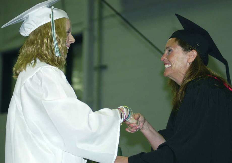 Ashley Billings receives her diploma from Board of Education chairwoman Wendy Faulenbach during New Milford High School's commencement exercises at the O'Neill Center on the campus of Western Connecticut State University in Danbury. June 22, 2013 Photo: Norm Cummings