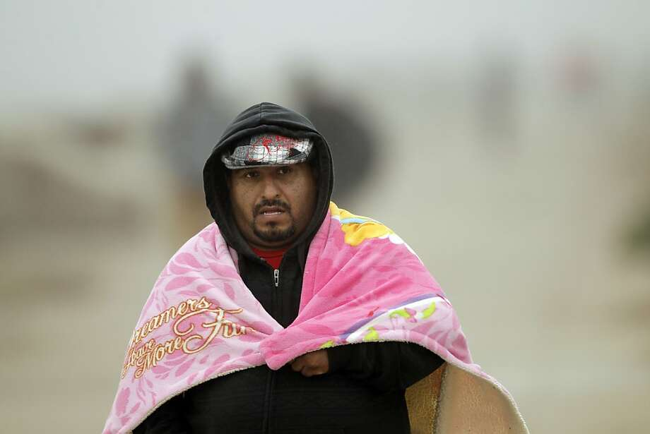 Rodolfo Sotelo of San Jose bundles up as he walks down Ocean Beach during the arrival of a late-season storm. Photo: Carlos Avila Gonzalez, The Chronicle