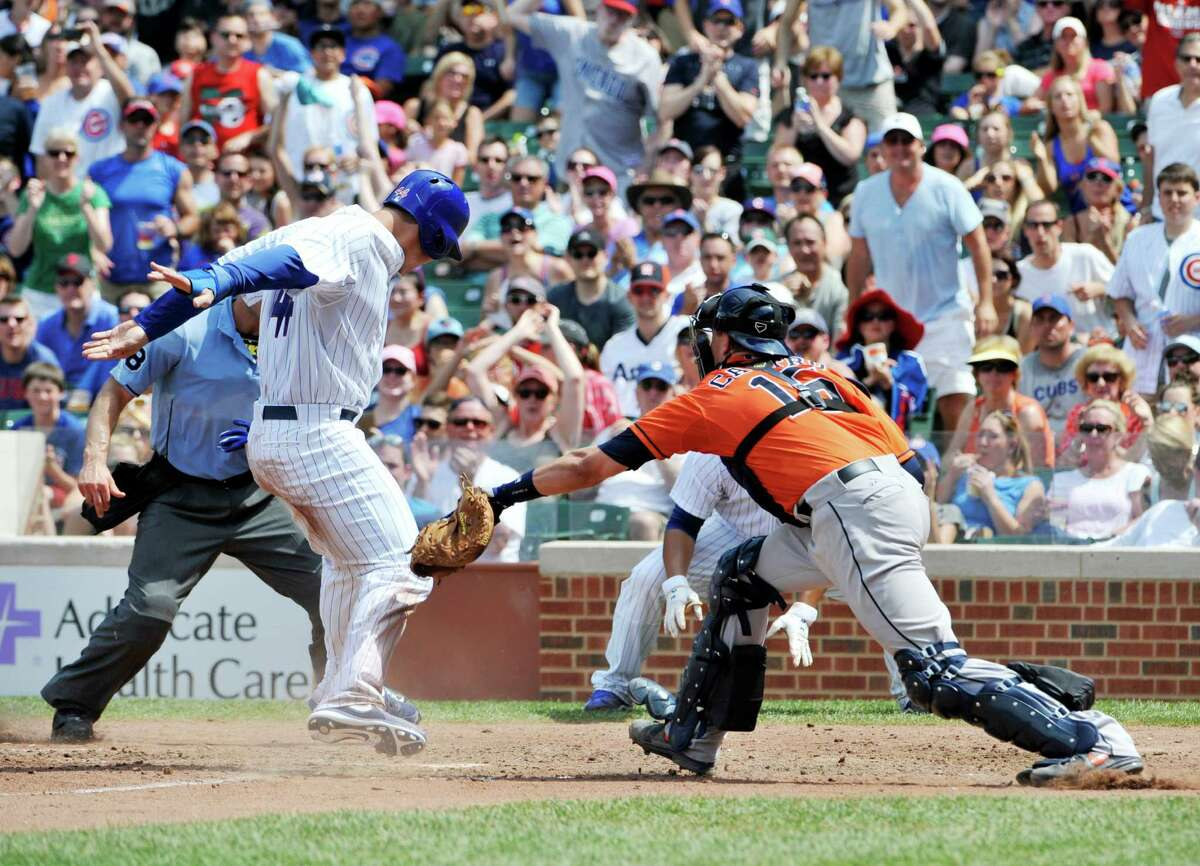 Cubs first baseman Anthony Rizzo, left, plays a form of dodgeball, avoiding the tag of Astros catcher Jason Castro, to score on Ryan Sweeney's double in the fifth inning.