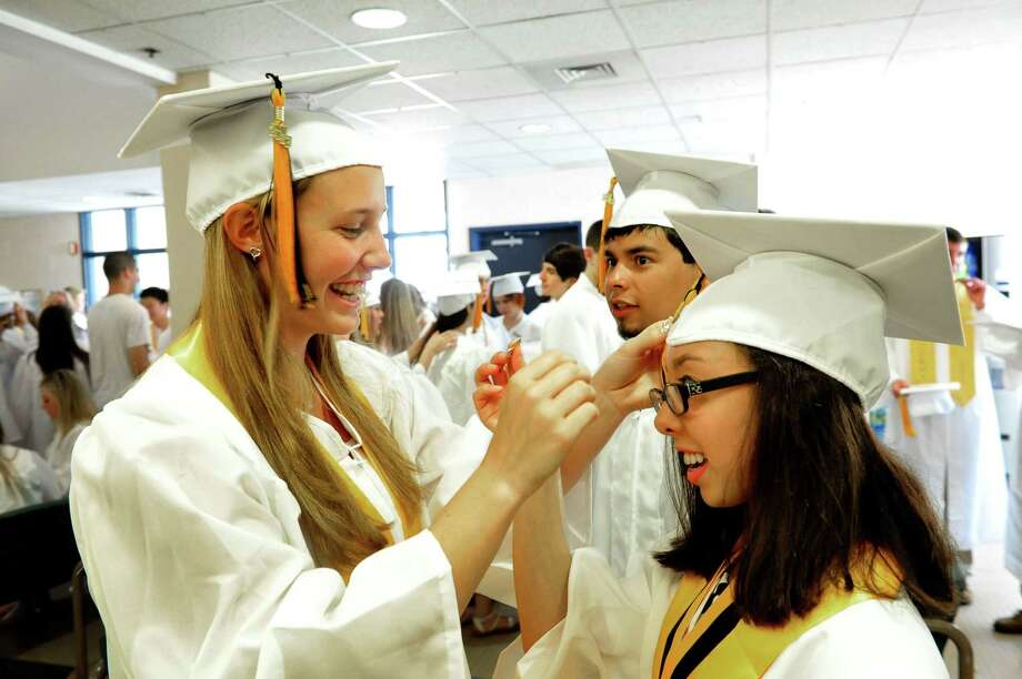 Devon De Lallo fixes Brooklee Han's cap as Joel Barlow High School Class of 2013 holds commencement ceremonies at the O'Neill Center, on the campus of Western Connecticut State University, in Danbury, Conn. Sunday, June 23, 2013. Photo: Michael Duffy / The News-Times