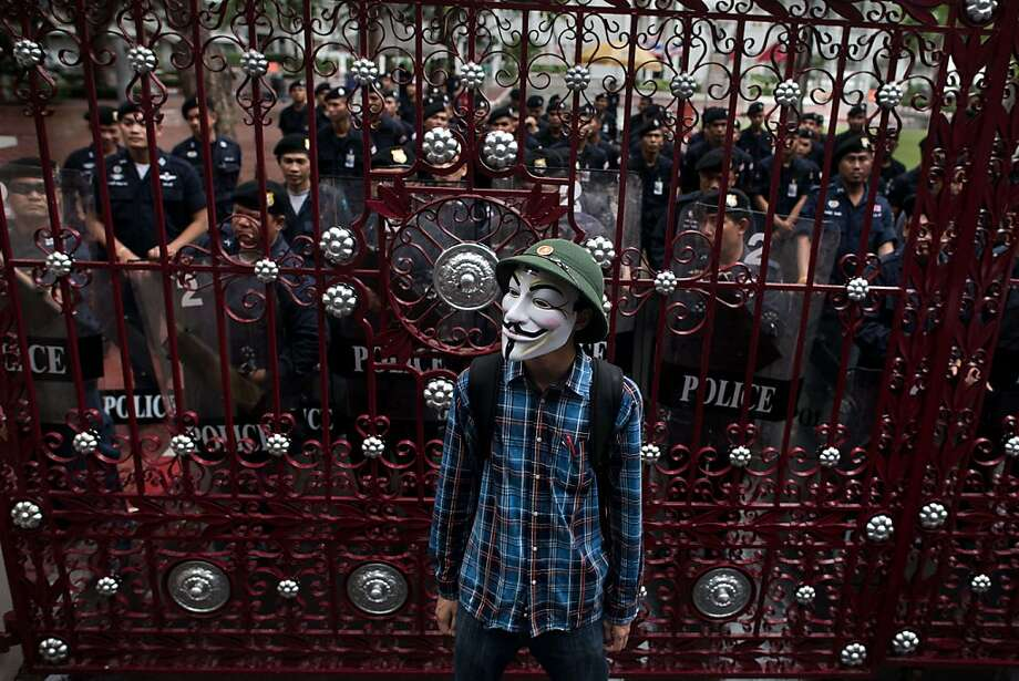 TOPSHOTS A protester wearing a Guy Fawkes mask, stand in front of a gate secured by Thai police officers as he and thousands of protesters gather in Bangkok's shopping district on June 23, 2013. Thousands of people marched through central Bangkok to protest against the former prime minister Thaksin Shinawatra and the current government led by his sister Thai Prime minister Yingluck Shinawatra. AFP PHOTO/ Nicolas ASFOURINICOLAS ASFOURI/AFP/Getty Images Photo: Nicolas Asfouri, AFP/Getty Images