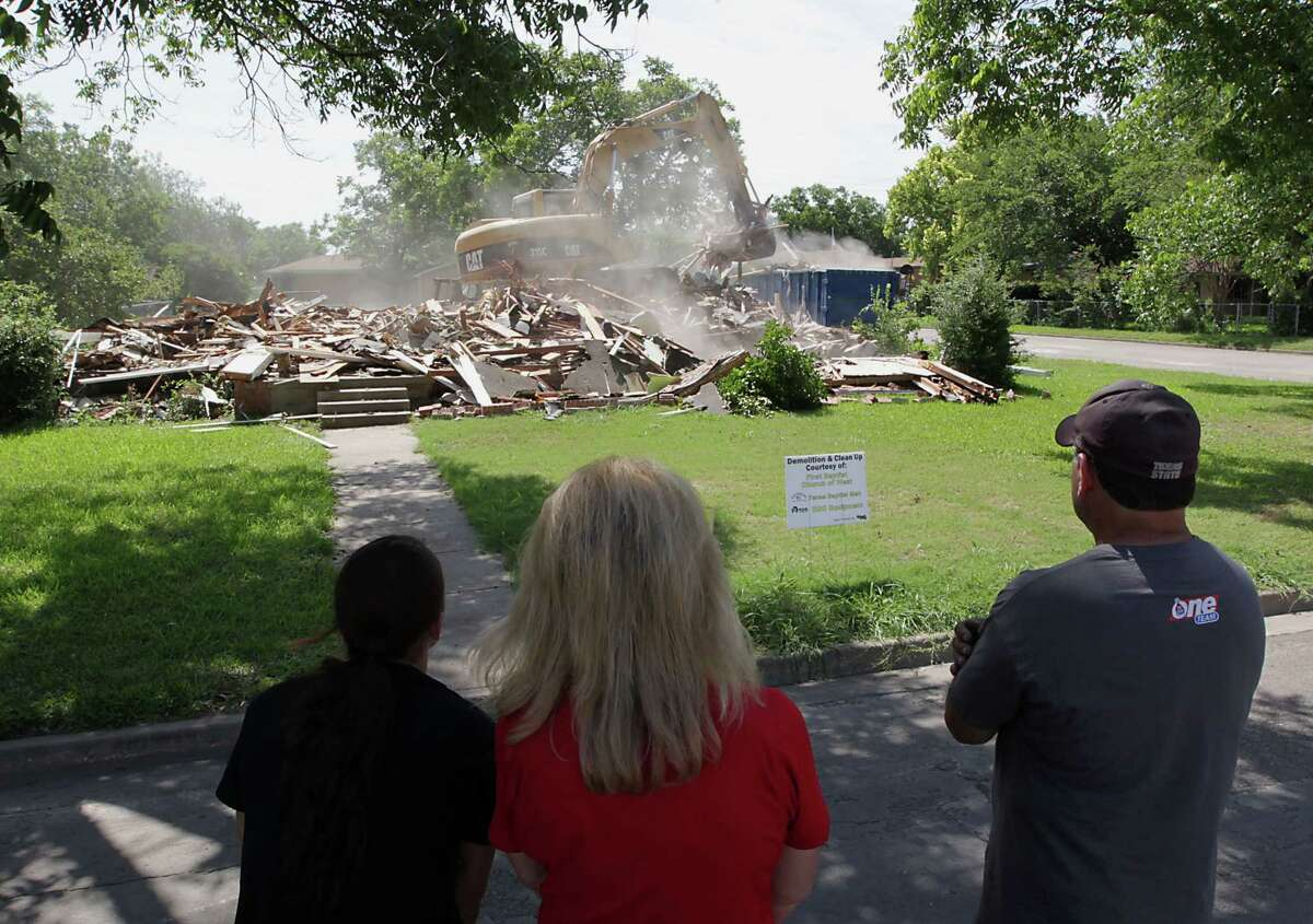 """Debbie Keel, center, watches this month as her childhood home is demolished with daughter Brooke Keel, left, and husband Ernie Keel. The home was damaged in the fatal April blast at West Fertilizer Co. """"If it was just gone, we could move on,"""" she said."""