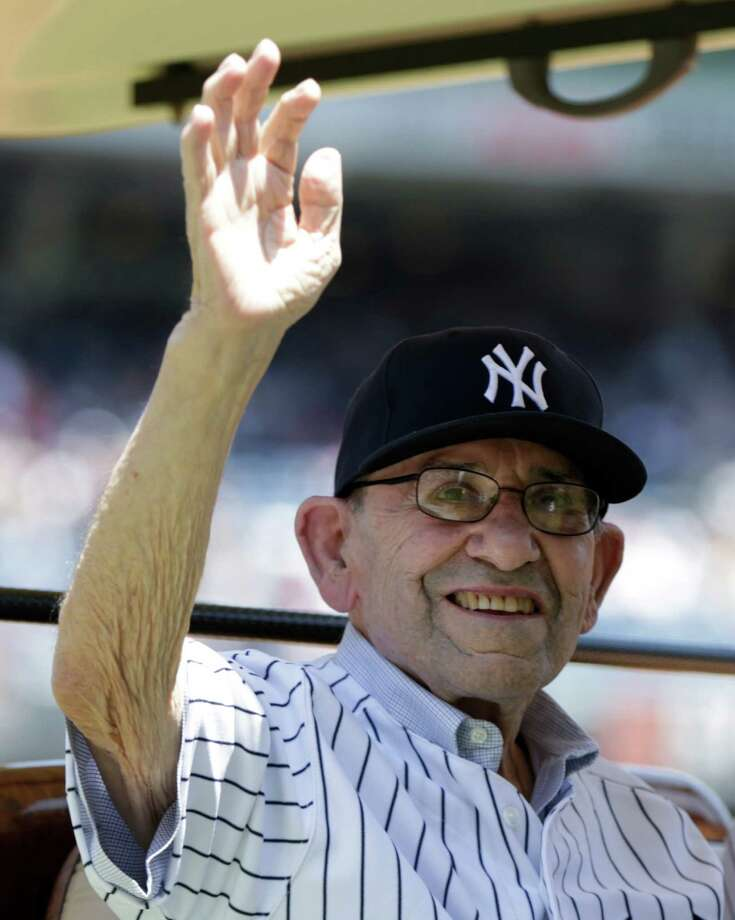 Hall of Fame catcher Yogi Berra waves to the crowd as he is introduced before the Yankees Old Timers Day baseball game Sunday, June 23, 2013, in New York. (AP Photo/Kathy Willens) Photo: Kathy Willens