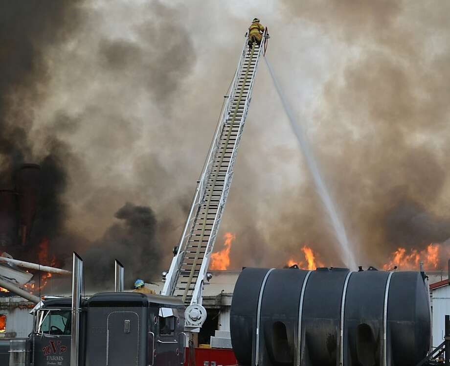 Firefighters from at least three area departments work to douse flames as they engulf a Scribner Grain facility Sunday morning, June 23, 2013, along U.S. Highway 275 in Scribner, Neb.  (AP Photo/The Tribune, Tracy Buffington) Photo: Tracy Buffington, Associated Press