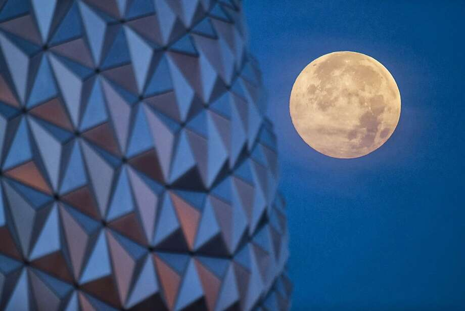 "LAKE BUENA VISTA, FL - JUNE 23: In this handout photo provided by Disney Parks, the ""supermoon"" is seen with the Epcot center geodesic sphere in the foreground on June 23, 2013 at Walt Disney World Resort in Lake Buena Vista, Florida. This ""supermoon"" is the closest and largest full moon for all of 2013. A ""supermoon"" will not occur again until August 10, 2014. (Photo by David Roark/Disney Parks via Getty Images) Photo: Handout, Getty Images"