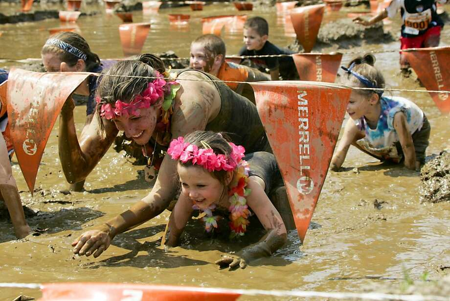 In this photo provided by Michael Epstein Sports Production (MESP), a woman and child crawl through a mud pit during the Matchbox 100 yard dash at the Merrell, Down and Dirty competition in Hartford, Conn., on Sunday, June 23, 2013. (AP Photo/MESP, Michael Epstein Sports Production, Nathan Bilow) Photo: Nathan Bilow, Associated Press
