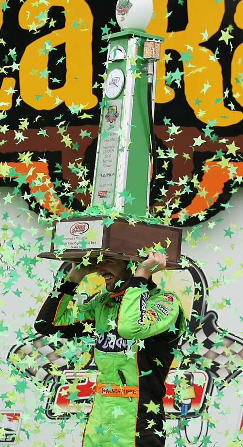 James Hinchcliffe uses his trophy to shield himself from confetti in Victory Lane after winning the IndyCar series auto race in Newton, Iowa, Sunday June 23, 2013. (AP Photo/Justin Hayworth) Photo: Justin Hayworth, Associated Press