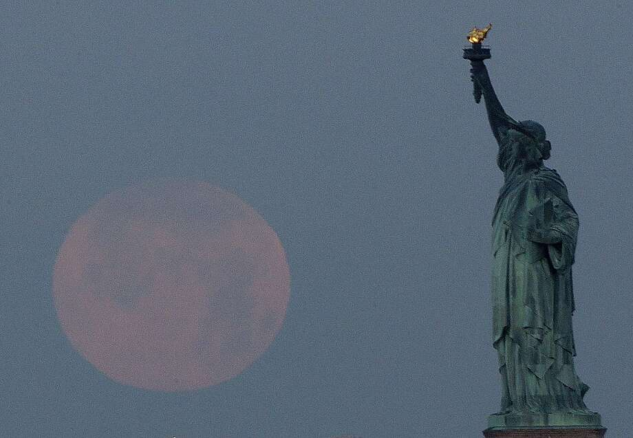 "A supermoon sets near the Statue of Liberty, Sunday, June 23, 2013, in New York. The larger than normal moon called the ""Supermoon"" happens only once this year as the moon on its elliptical orbit is at its closest point to earth and is 13.5 percent larger than usual. (AP Photo/Julio Cortez) Photo: Julio Cortez, Associated Press"