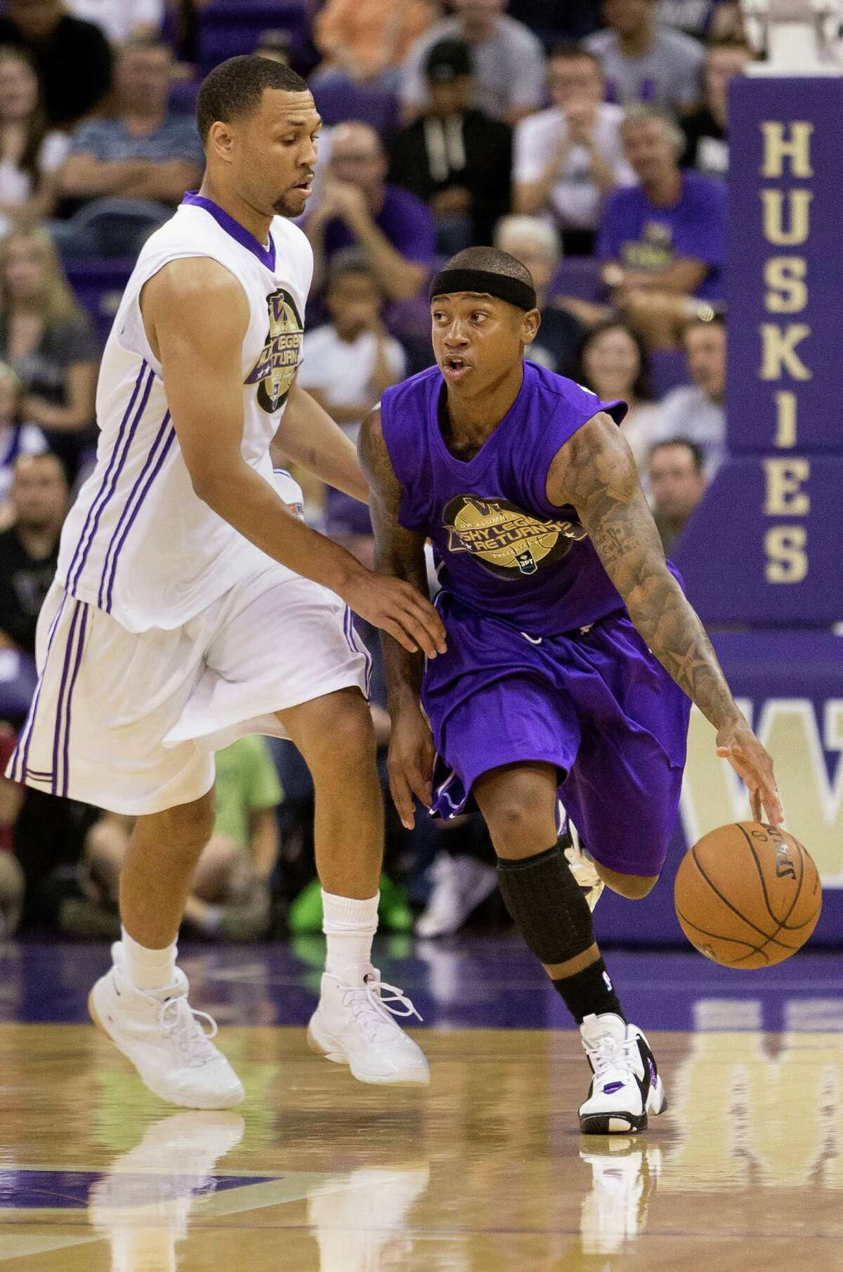 Isaiah Thomas, right, pushes past Brandon Roy, left, during the University of Washington Alumni Game Sunday, June 23, 2013, in the Alaska Airlines Arena at the University of Washington in Seattle, Wash. The after-2009 team, in purple, beat the pre-2009 team, in white, 107-104.