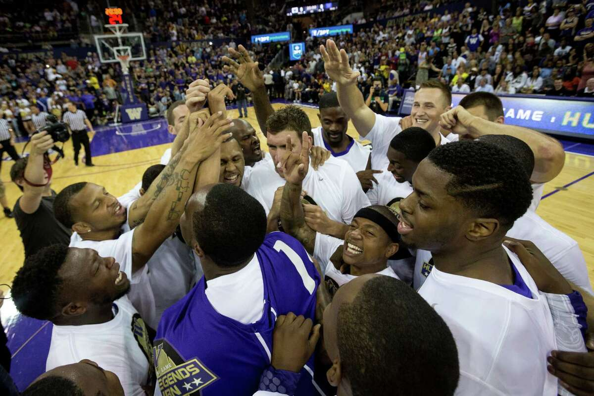Isaiah Thomas, center right, is mobbed by teammates at the beginning of the University of Washington Alumni Game Sunday, June 23, 2013, in the Alaska Airlines Arena at the University of Washington in Seattle, Wash. The after-2009 team, in purple, beat the pre-2009 team, in white, 107-104.
