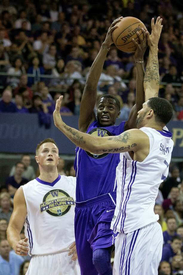 Justin Holiday, center, pushes past defense on his way to the hoop during the University of Washington Alumni Game Sunday, June 23, 2013, in the Alaska Airlines Arena at the University of Washington in Seattle. The after-2009 team, in purple, beat the pre-2009 team, in white, 107-104. Photo: JORDAN STEAD, SEATTLEPI.COM / SEATTLEPI.COM