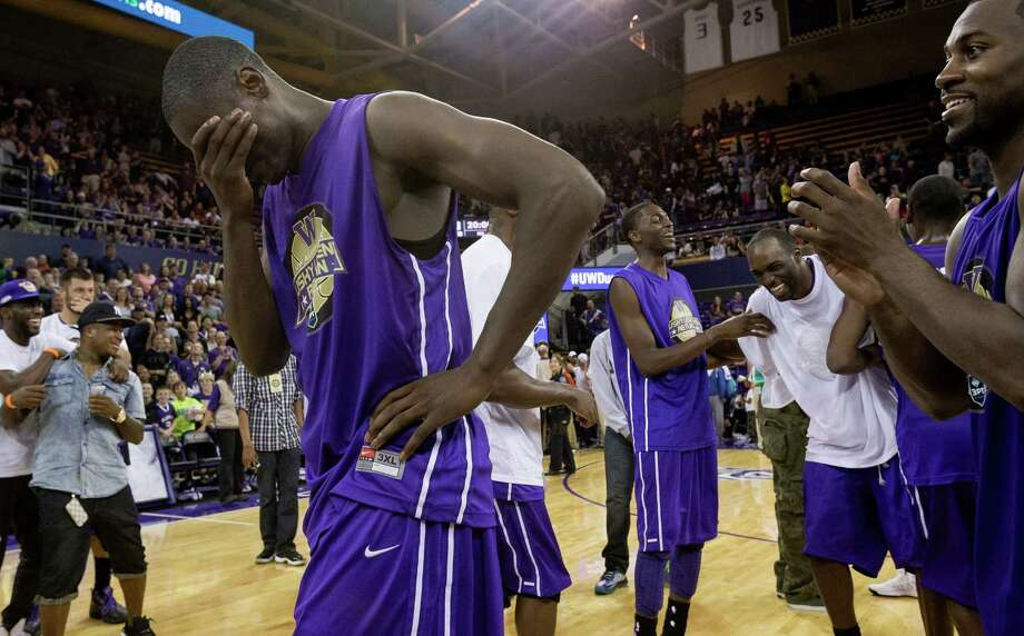 Darnell Gant, left, hams up a reaction following his victory in the slam dunk contest following the University of Washington Alumni Game Sunday, June 23, 2013, in the Alaska Airlines Arena at the University of Washington in Seattle, Wash. The after-2009 team, in purple, beat the pre-2009 team, in white, 107-104. Photo: JORDAN STEAD, SEATTLEPI.COM / SEATTLEPI.COM