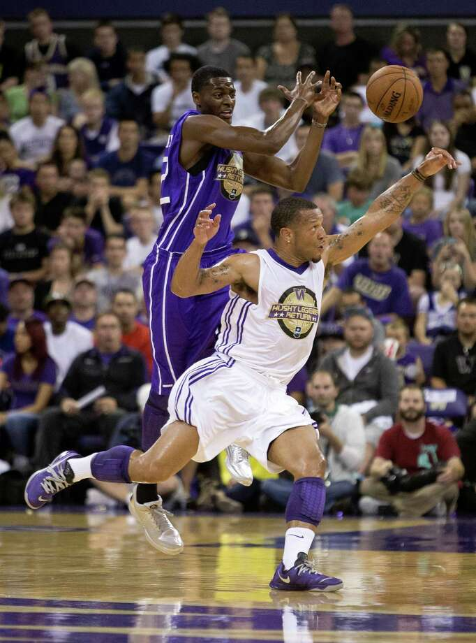 Will Conroy, foreground, and Justin Holiday, background, compete for a loose ball during the University of Washington Alumni Game Sunday, June 23, 2013, in the Alaska Airlines Arena at the University of Washington in Seattle, Wash. The after-2009 team, in purple, beat the pre-2009 team, in white, 107-104. Photo: JORDAN STEAD, SEATTLEPI.COM / SEATTLEPI.COM