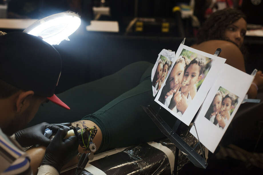 Mike Diaz of Lubbock tattoos Keirstin Porter at the Alamo City Tattoo Show at Crowne Plaza San Antonio Riverwalk Hotel. Porter, who is in the Navy and stationed at Fort Sam Houston, was getting a tattoo of her and her brother, Jerry. Photo: Abbey Oldham / San Antonio Express-News