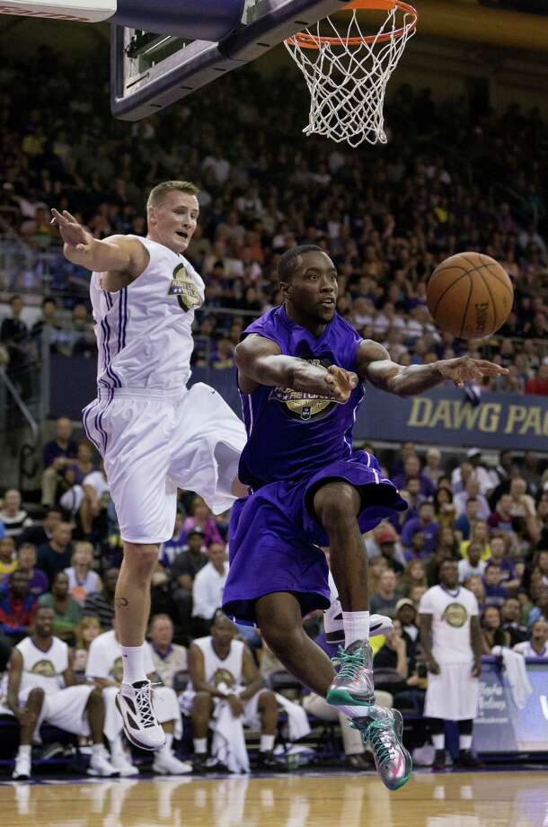 Tony Wroten, right, makes a last second pass away to a teammate after heading for the hoop during the University of Washington Alumni Game Sunday, June 23, 2013, in the Alaska Airlines Arena at the University of Washington in Seattle, Wash. The after-2009 team, in purple, beat the pre-2009 team, in white, 107-104. Photo: JORDAN STEAD, SEATTLEPI.COM / SEATTLEPI.COM