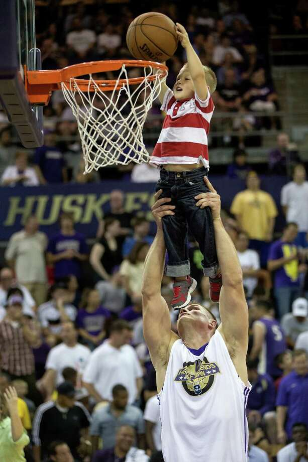 Mike Jensen, bottom, lifts his son, Jacob Jensen, 3, top, to reach the basket during a timeout at the University of Washington Alumni Game Sunday, June 23, 2013, in the Alaska Airlines Arena at the University of Washington in Seattle. The after-2009 team, in purple, beat the pre-2009 team, in white, 107-104. Photo: JORDAN STEAD, SEATTLEPI.COM / SEATTLEPI.COM