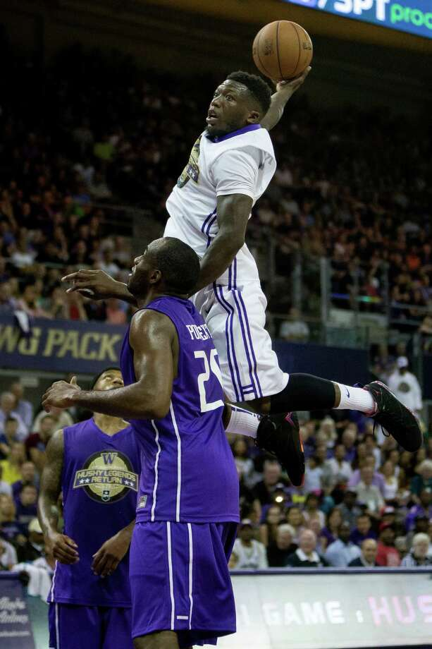 Nate Robinson, top, uses Quincy Pondexter, bottom, as a lift for a dunk at the University of Washington Alumni Game Sunday, June 23, 2013, in the Alaska Airlines Arena at the University of Washington in Seattle. The after-2009 team, in purple, beat the pre-2009 team, in white, 107-104. Photo: JORDAN STEAD, SEATTLEPI.COM / SEATTLEPI.COM