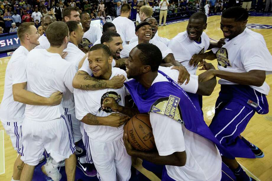 Will Conroy, center left, is mobbed by teammates at the beginning of the University of Washington Alumni Game Sunday, June 23, 2013, in the Alaska Airlines Arena at the University of Washington in Seattle, Wash. The after-2009 team, in purple, beat the pre-2009 team, in white, 107-104. Photo: JORDAN STEAD, SEATTLEPI.COM / SEATTLEPI.COM