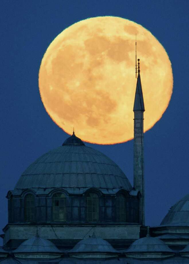 The supermoon rises behind a building of the Topkapi Palace in Istanbul, Turkey. The moon, which will reach its full stage on Sunday, is expected to be 13.5 percent closer to earth during a phenomenon known as supermoon. Photo: Gero Breloer, Associated Press / AP