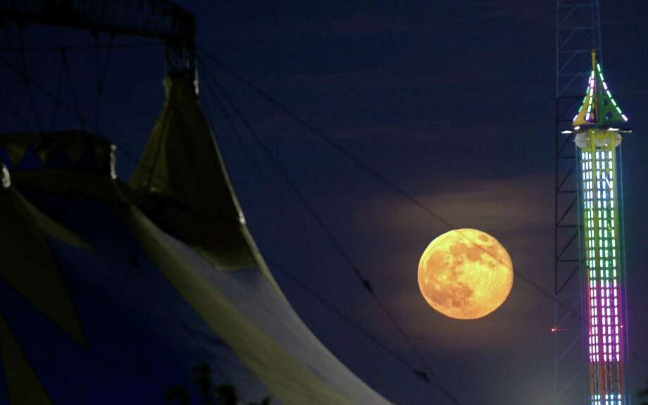 The moon rises between a tent, left, and a ride at State Fair Meadowlands, in East Rutherford, N.J. The so-called supermoon appeared up to 14 percent larger than normal this weekend as our celestial neighbor swung closer to Earth, reaching its closest distance early Sunday morning. Photo: Julio Cortez, Associated Press / AP